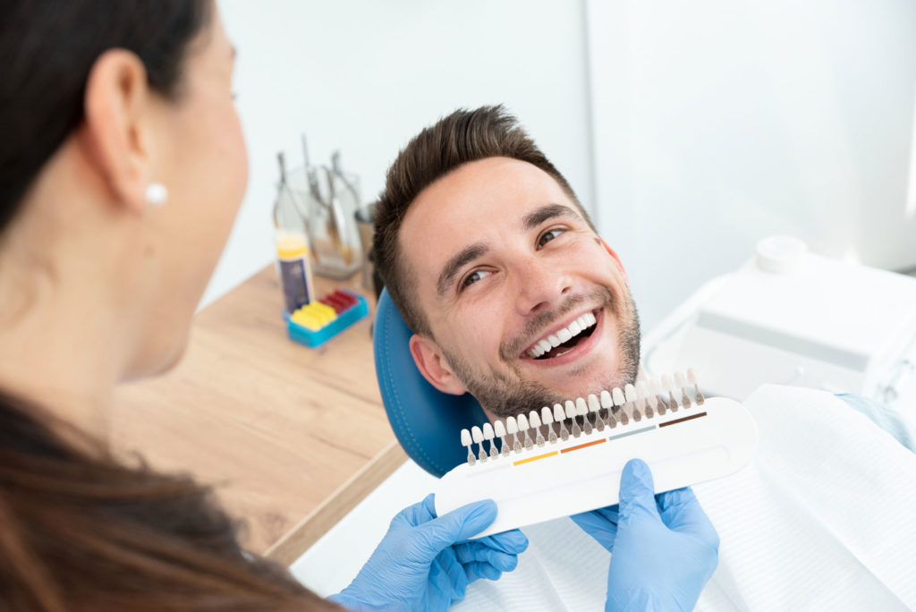 All-on-four fixed-bridge patient smiling, hygienist showing diagram