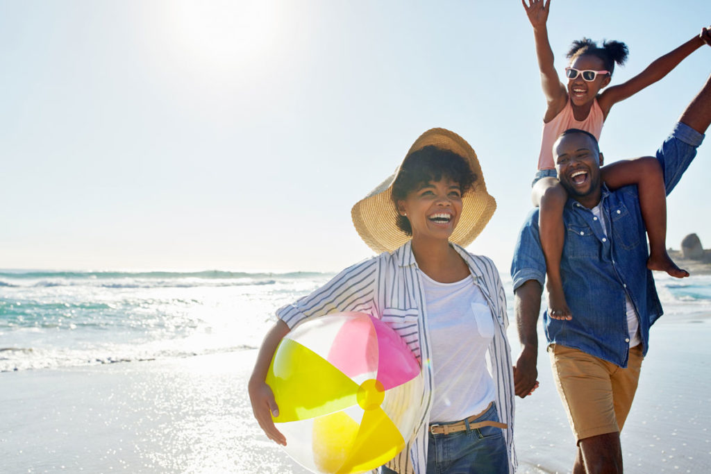 Family on beach, smiling, beach ball